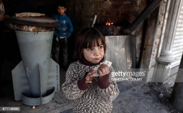 A Syrian girl eats a bread which was baked in a makeshift oven using the remains of a rocket by 45yearold house painter and artist Abu Ali alBitar in...