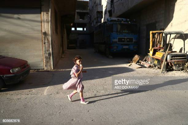 A Syrian girl eats icecream as she walks in the street on the third day of the AlAdha Eid Muslim holiday in the rebelcontrolled town of Hamouria in...