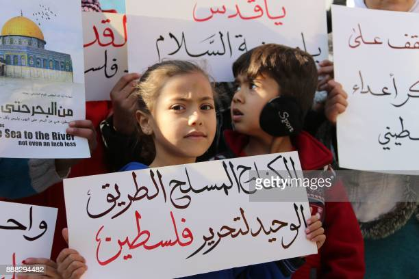 A Syrian girl holds a banner that reads in Arabic 'Armed struggle is the only way to liberate Palestine' during a protest after the Friday prayers...