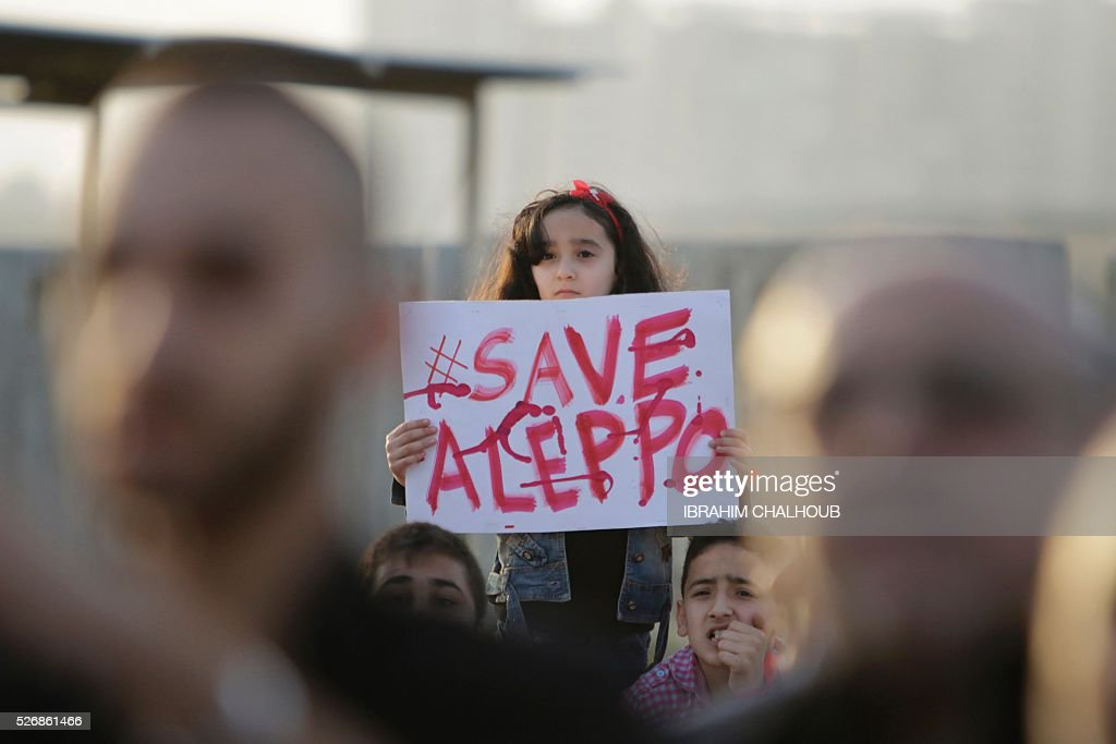 A Syrian girl holds a placard during a rally in solidarity with Aleppo, in the Lebanese northern port city of Tripoli, on May 1, 2016. More than a week of fighting in Syria's second city has killed hundreds of civilians and left a UN-backed peace process hanging by a thread. Concern has been growing that the fighting in Aleppo will lead to the complete collapse of a landmark ceasefire between President Bashar al-Assad's regime and non-jihadist rebels that was brokered by Moscow and Washington. / AFP / IBRAHIM