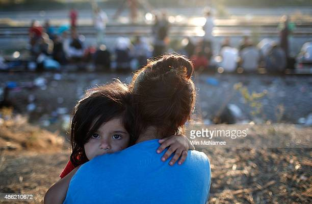 Syrian girl is held by her mother as they wait to be processed through a border crossing into Macedonia for migrants September 2 2015 in Idomeni...