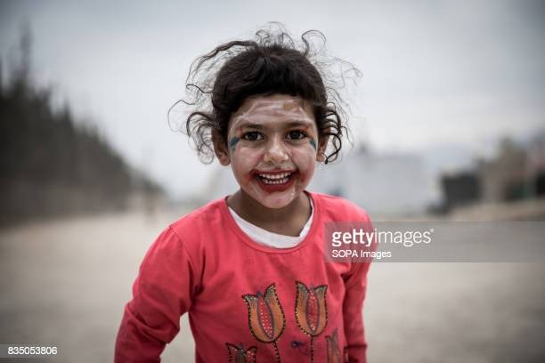 Syrian girl is pictured with faceprint draw on her face in a refugee settlement