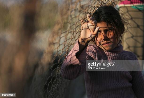 A Syrian girl leans onto a wire fence at the Ash'ari camp for the displaced in the rebelheld eastern Ghouta area outside the capital Damascus on...