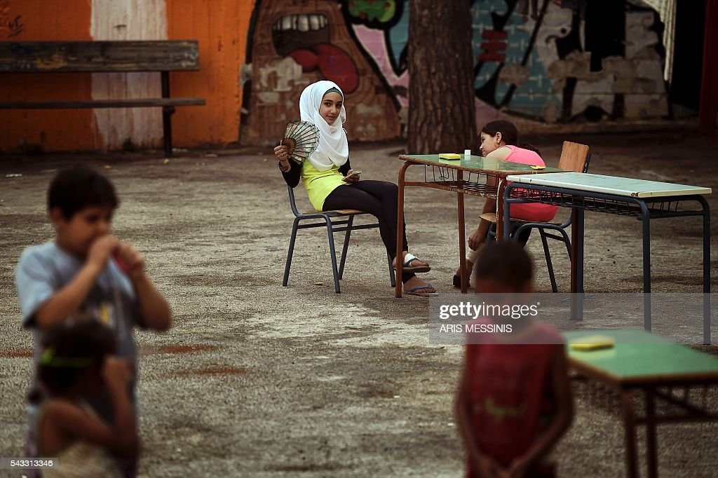 A Syrian girl looks on as she sits at the yard of an abandoned school used by volunteers for hosting families of refugeees from Syria and Afghanistan in Athens on June 27, 2016. / AFP / ARIS