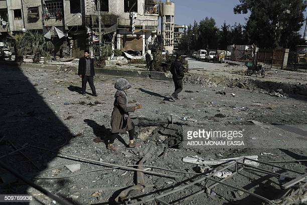A Syrian girl makes her way through debris following reported air strikes in Hammuriyeh in the rebelheld Eastern Ghouta area on the outskirts of the...