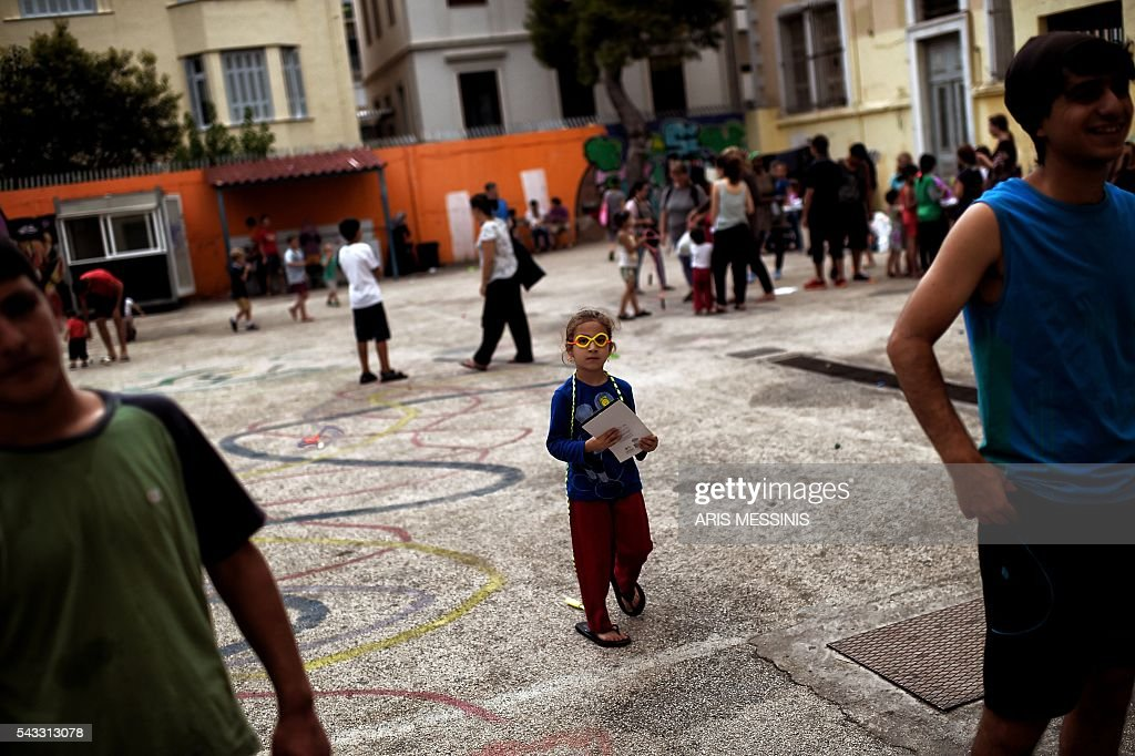 A Syrian girl plays at the yard of an abandoned school used by volunteers for hosting families of refugeees from Syria and Afghanistan in Athens on June 27, 2016. / AFP / ARIS