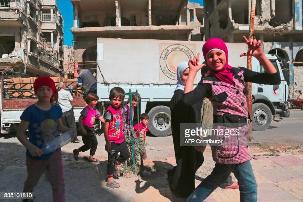 A Syrian girl reacts as she walks past a Syrian Arab Red Crescent truck carrying aid in the rebelheld town of Douma on the eastern outskirts of...