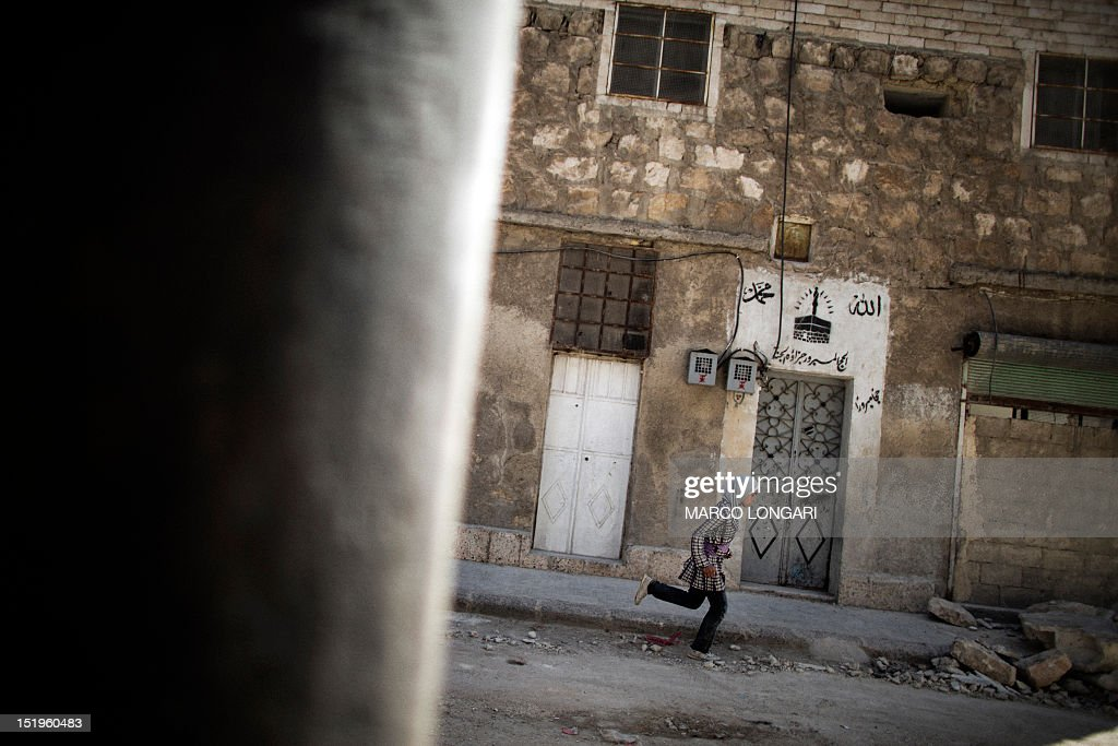 A Syrian girl runs for cover from a air raid in Aleppo on September 13, 2012. Peace envoy Lakhdar Brahimi said the deadly conflict in Syria was getting worse as he arrived on his first official trip aimed at ending nearly 18 months of violence.