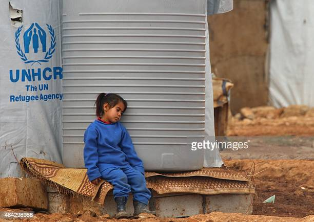 A Syrian girl sits next to a water tank at a refugee camp on the outskirts of the eastern Lebanese city of Baalbek on February 24 2015 More than 11...