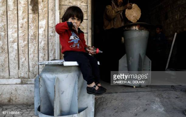 A Syrian girl sits on the remains of a rocket as 45yearold house painter and artist Abu Ali alBitar bakes bread in a makeshift oven using the remains...