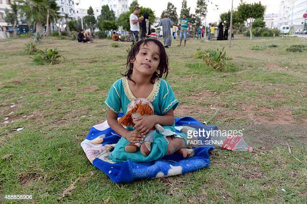 A Syrian girl sits with a doll on September 17 2015 at a park where around 1000 Syrians migrants are gathering in the Moroccan town of Nador waiting...