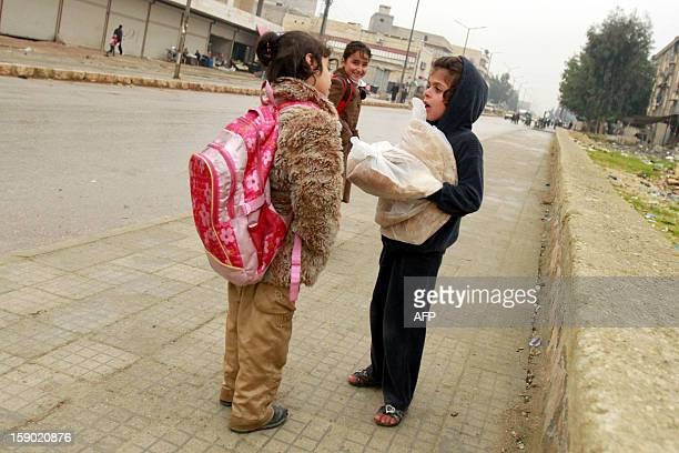 A Syrian girl talks with her friend in a street in a neighbourhood in the northern city of Aleppo on January 5 2013 Saudi Arabia and Egypt called for...