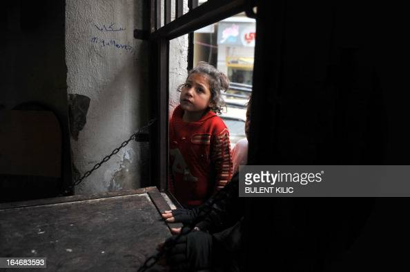 A Syrian girl waits to receive food aid in the Bustan alQasr district of the northern city of Aleppo on March 26 2013 Rebels won Syria's longvacant...
