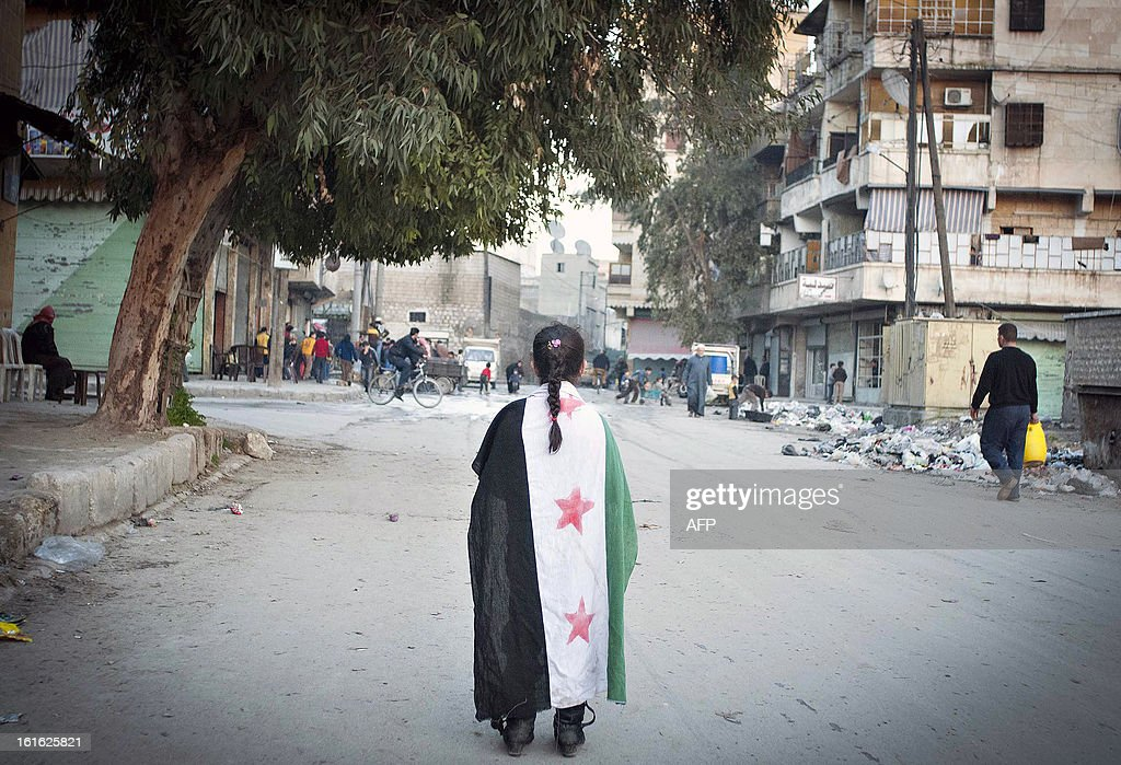 A Syrian girl walks along a street with the pre-Baath Syrian flag across, now adopted by the Free Syrian Army, across her shoulders in the city of Aleppo on February 13, 2013. Syrian rebels took control of most of a strategic army base in northern Syria after a fierce firefight with President Bashar al-Assad's forces, a monitoring group said.