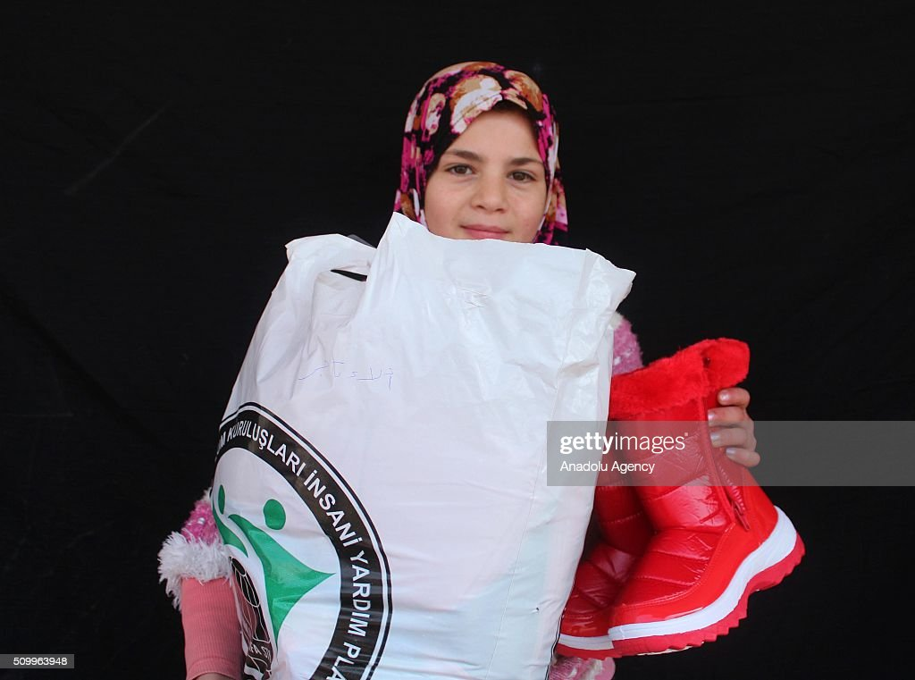 A Syrian girl, who has lost her parents in the country's civil war, poses after the Sanliurfa Humanitarian Aid Platform provided clothes and toys to her in Sanliurfa, Turkey on February 13, 2016. The platform, which was established to carry out activities to help Syrian children, gave joy to children who had lost their parents in the Suleiman Shah camp. 115 children were brought to the Sanliurfa Humanitarian Aid Platform Charity Shop by minibuses to choose clothes for themselves.