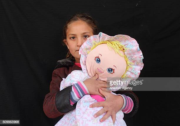 Syrian girl who has lost her parents in the country's civil war poses after the Sanliurfa Humanitarian Aid Platform provided clothes and toys to her...