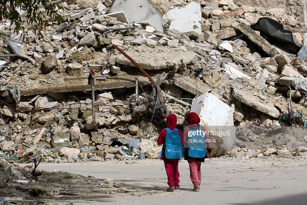 Syrian girls, carrying school bags provided by UNICEF, walk past the rubble of destroyed buildings on their way home from school on March 7, 2015 in al-Shaar neighbourhood, in the rebel-held side of the northern Syrian city of Aleppo. Heavy fighting shook the Syrian city of Aleppo on march 6, 2015 as the exiled opposition chief said for the first time that President Bashar al-Assad's ouster need not be a pre-condition for peace talks.