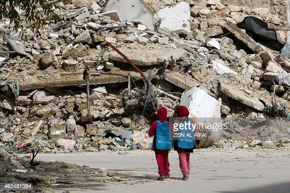 Syrian girls carrying school bags provided by UNICEF walk past the rubble of destroyed buildings on their way home from school on March 7 2015 in...