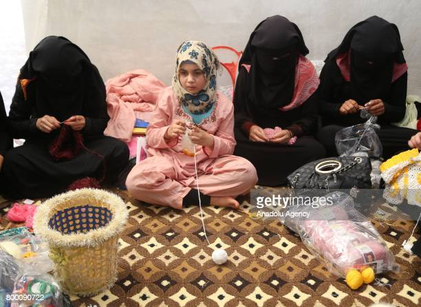Syrian girls crochet inside their tent during Muslim's holy month of Ramadan in Idlib Syria on June 23 2017 Ahead of Eid al Fitr Syrian people who...