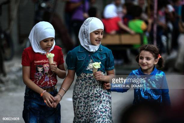Syrian girls eat ice cream in the rebelheld town of Douma on the eastern edges of the capital Damascus on September 14 on the third day of Eid alAdha...