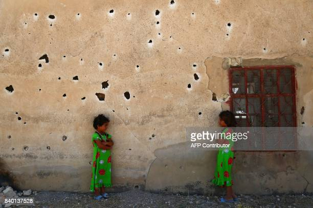 TOPSHOT Syrian girls pose for a photograph against a bulletriddled wall in the rebelheld village of Kafr Ghan in the northern countryside of Aleppo...