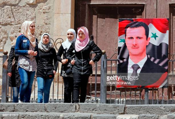 Syrian girls stands next to a poster of Syrian President Bashar alAssad in the old city of Damascus on May 25 2017 / AFP PHOTO / Louai Beshara