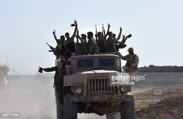 Syrian government forces celebrate in the eastern Syrian city of Deir Ezzor on September 11 2017 as they continue to press forward with Russian air...