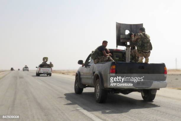 Syrian government forces drive on a road in Kobajjep area on the southwestern outskirts of Deir Ezzor on September 5 during the ongoing battle...