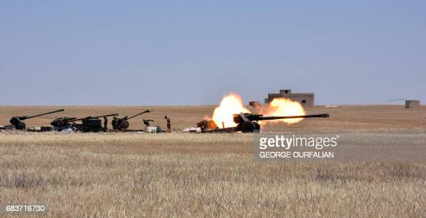 Syrian government forces fire artillery during a battle against the Islamic State group on May 16 2017 in the town of Maskana on the edge of Lake...