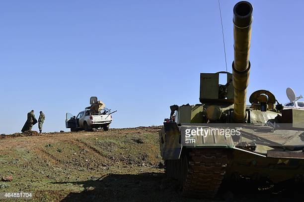 Syrian government forces gather on the Fatima hill overlooking the town of Kfar Shams north of the southern Syrian city of Deraa on March 1 after...