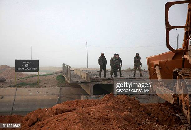 Syrian government forces look at a bridge broken by Islamic State group fighters connecting the village of alTiba with Aleppo's thermal power plant...