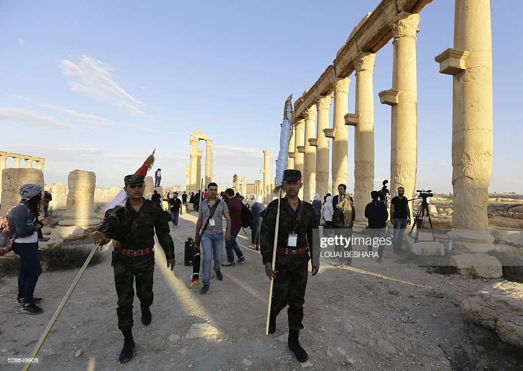 Syrian government forces march at the ancient historical site of Syria's ravaged Palmyra on May 6, 2016 ahead of a music concert following its recapture by regime forces from the Islamic State group fighters. Syrian troops backed by Russian air strikes and special forces on the ground recaptured UNESCO world heritage site Palmyra from Islamic State (IS) group fighters in March 2016. BESHARA