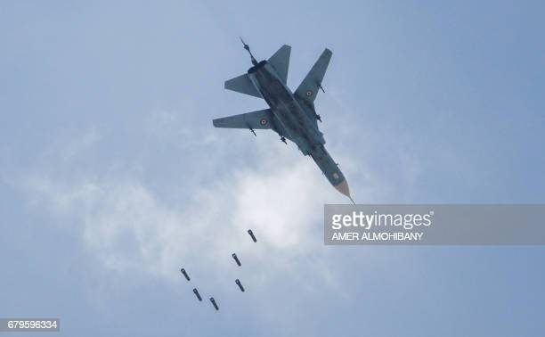 A Syrian government forces' MiG23 fighterbomber drops a payload during a reported air strike in the rebelheld area of Qabun east of the capital...