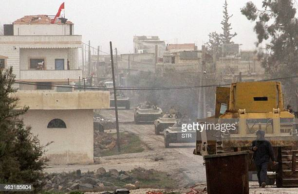 Syrian government forces' military vehicles are seen in Deir alAdas in the Daraa province on February 11 2015 after President Bashar alAssad's army...