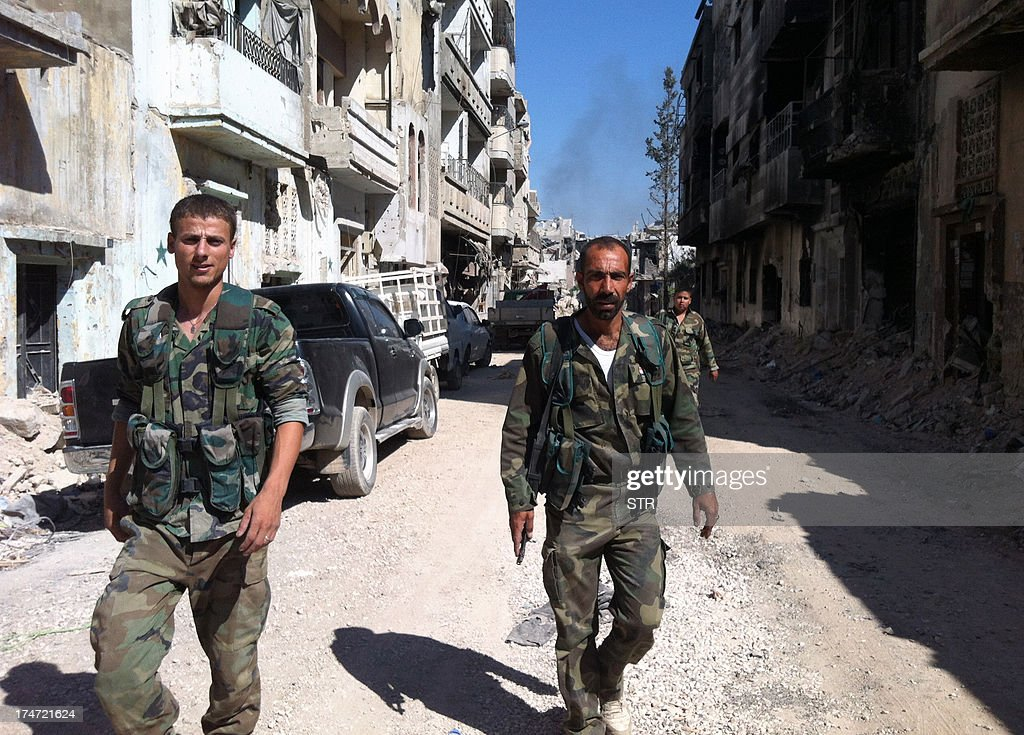 Syrian government forces patrol the Khalidiyah neighbourhood of the central city of Homs on July 28, 2013. Government forces bolstered by Lebanese Shiite militiamen were poised to retake the largest rebel-held district of Syria's third city Homs, a watchdog and state media said.