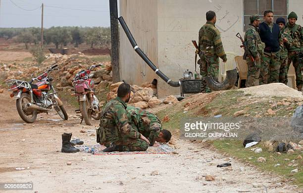 Syrian government forces pray after taking control of the Kiffin on the northern outskirts of the embattled city of Aleppo on the road leading to...