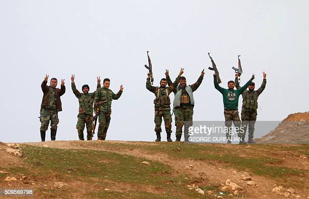 TOPSHOT Syrian government forces raise their weapons as they patrol after taking control of the village of Kiffin on the northern outskirts of the...