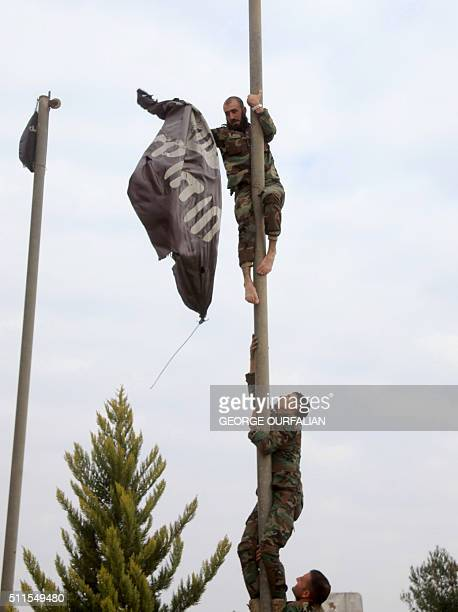 Syrian government forces remove an Islamic State group flag and replace it with a Syrian flag at Aleppo's thermal power plant after they retook...