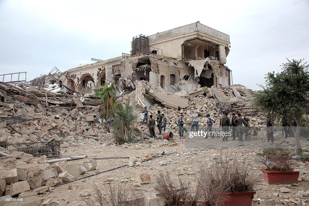 Syrian government forces sift through the rubble on May 8 2014 following an explosion at luxury hotel turned army base in the historic heart of...