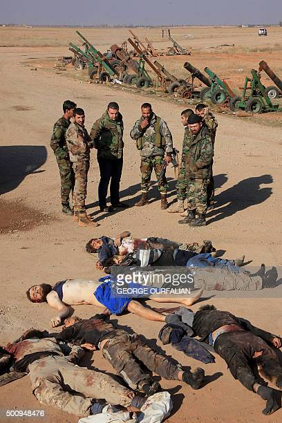 Syrian government forces stand near the bodies of reported members of the Islamic State group who were killed during a battle with regime forces in...