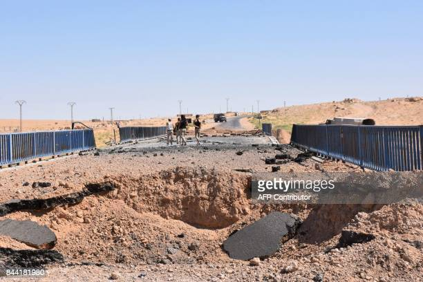TOPSHOT Syrian government forces stand next to a destroyed bridge on a road between the Kabajeb and AlShula on the southwestern outskirts of Deir...