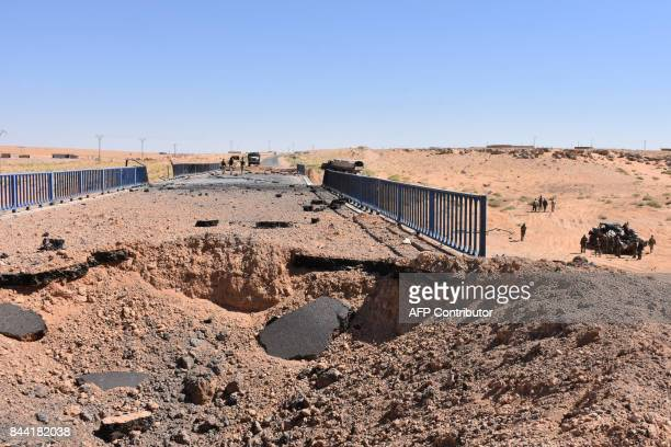 Syrian government forces stand next to a destroyed bridge on a road between the Kabajeb and AlShula on the southwestern outskirts of Deir Ezzor on...