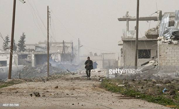 Syrian government forces walk in Deir alAdas in the Daraa province on February 11 2015 after President Bashar alAssad's army backed by Hezbollah and...
