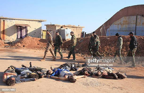 TOPSHOT Syrian government forces walk past the bodies of reported members of the Islamic State group who were killed during a battle with regime...