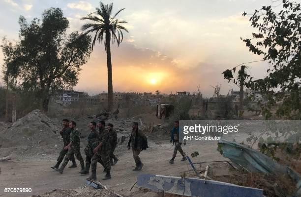 TOPSHOT Syrian government forces walk through a road in a northeastern district of Deir Ezzor on November 5 after retaking the city from Islamic...