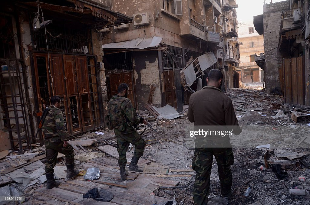 Syrian government forces walk through the destruction in the old souk of the northern Syrian city of Aleppo on January 3, 2013, after they allegedly recaptured the area from opposition forces. Rebels launched assaults to try to take strategic airports in northern Syria, after the United Nations revealed that the country's civil war had already killed 60,000 people. AFP PHOTO /STR