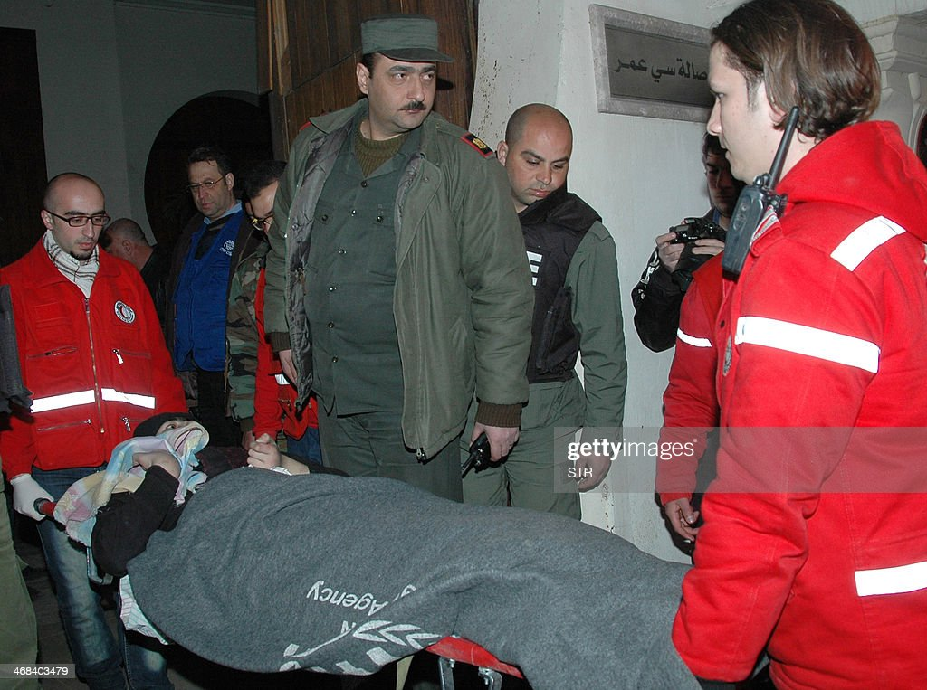 Syrian government forces watch as Red Crescent staff wheel a wounded woman on a stretcher after civilians were evacuated from rebel-controlled districts that were besieged by the army, into a government-ruled area, in the central Syrian city of Homs, on February 10, 2014. A deal brokered by the UN has allowed aid teams access to Homs for four consecutive days, with a fragile ceasefire in place to allow the humanitarian operation. Some 300 people were evacuated today from army-besieged districts of Syria's Homs. The latest evacuations bring the total number of civilians given safe passage out of the war-ravaged central part of the city up to some 1,000.