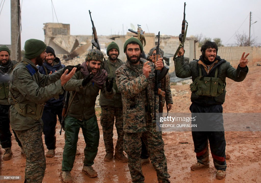 Syrian government soldiers celebrate after taking control of the village of Ratian, north of the embattled city of Aleppo, from rebel fighters on February 6, 2016. Thousands of Syrians fled towards Turkey as regime troops pressed a major Russian-backed offensive around Aleppo, that threatens a fresh humanitarian disaster. OURFALIAN