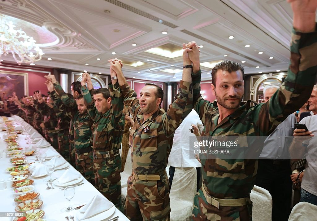 Syrian government soldiers dance during a dinner following their group wedding ceremony consisting of twenty couples in Damascus on April 29, 2014.