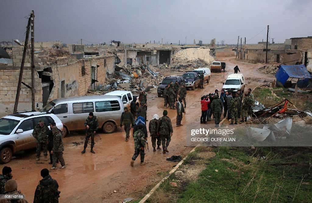 Syrian government soldiers re-group after taking control of the village of Ratian, north of the embattled city of Aleppo, from rebel fighters on February 6, 2016. Thousands of Syrians fled towards Turkey as regime troops pressed a major Russian-backed offensive around Aleppo, that threatens a fresh humanitarian disaster. OURFALIAN